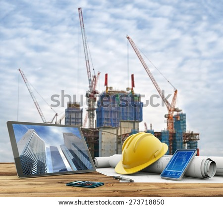 blueprints and safety helmet over a table in construction site