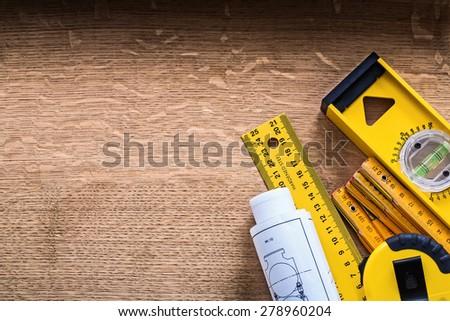 Blueprints and set of instruments of measurement on oak wood board construction concept