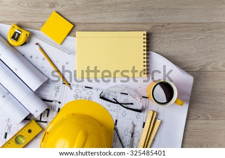 Blueprints, Hardhat, Glasses, Stickers, Construction level, Pen and Coffee in architecture office