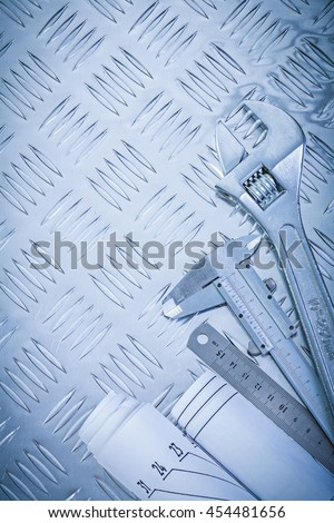 Free rolled construction drawings and stainless slide caliper on blueprints slide caliper monkey spanner on channeled metal background maintenance concept 454481656 malvernweather Images