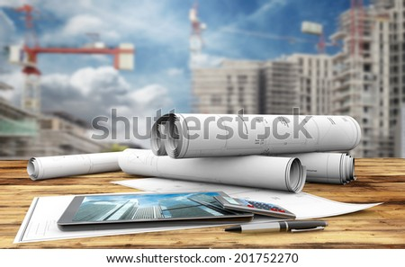 blueprints, tablet, calculator and pen in a construction site