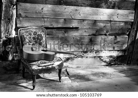 blues guitar on a old chair with wooden background horizontal black and white