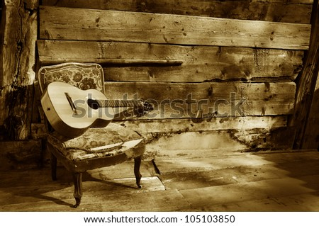 blues guitar on a old chair with wooden background horizontal brown