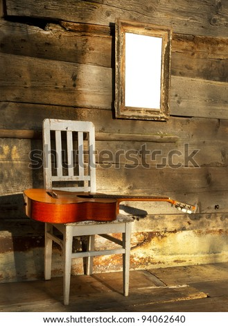 blues guitar on an old wooden chair at the wall with empty frame