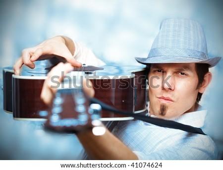 Bluesy musician holding his guitar - stock photo