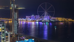 Bluewaters island aerial night timelapse with ferris wheel, new walking area with shopping mall and restaurants, newly opened leisure and travel spot in Dubai