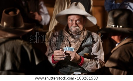 Bluffing card player in old American west saloon. Hands in focus.