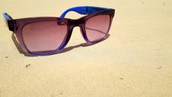 Bluish violet shade with shiny plastic frame on sand in desert in sunlight