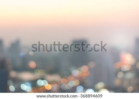 Blur abstract background aerial view Bangkok cbd downtown city night light colorful twilight skyline bokeh in warm vintage gold color tone: Central business district on electric train line over river