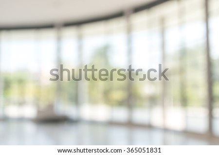 Blur abstract background exterior view looking out toward to empty office lobby and entrance doors/ glass curtain wall with frame: Blurry perspective of reception hall to public building entrance