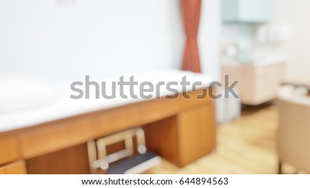 Blur abstract background inside empty patient examination room with bed in OPD ward. Blurry doctor desk for diagnosis sick people working space in hospital. Defocused interiors healthcare work place.