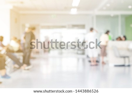 Blur abstract background of corridor in clean hospital. Blurry view of aisle in office with light floor. Defocus walkway in white light building hall with patient registration at reception desk.