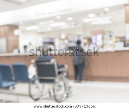 Blur abstract background perspective view of wheelchair seat row in hospital building interior/ clinical hallway indoor area w/ visitors patients waiting to see doctors, people paying money at cashier