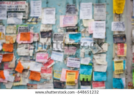 Blur abstract background with paper advertisements wall. Advertising notes. Outdoor bulletin board or plywood panel with worn advertising message, notice and stickers street texture. Creative surface. #648651232