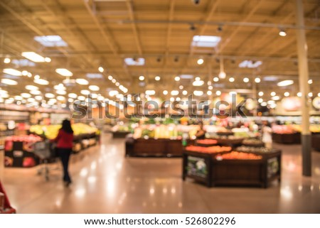 Blur abstract organic fresh produces, fruits and vegetable on shelves in store at Humble, Texas, US. Blurred supermarket, grocery with customers shopping, bokeh light background. Healthy concept.