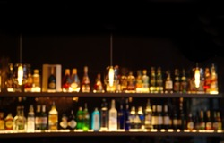 blur alcohol drink on bar counter in the dark night background