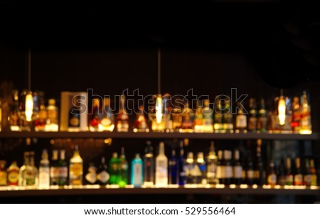 blur alcohol drink on bar counter in the dark night background #529556464