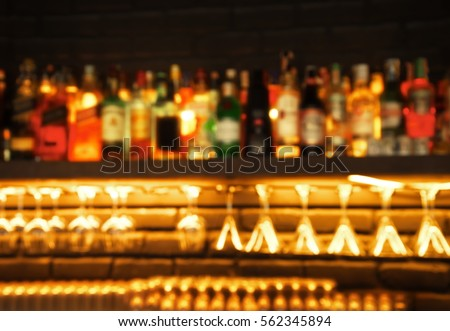 blur alcohol drinking bottle and glasses in the bar or pub at night background