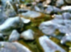 blur and defocused mini waterfall in the garden with black rocks for travel concept background, Blurred images of waterfalls in Thailand,
