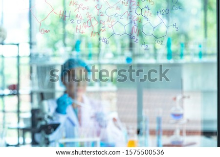 Blur Asian woman scientist, researcher, technician, or student conducted chemistry research and sitting after  glass board in laboratory
