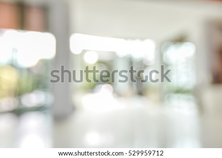 Blur background empty room of office building lobby with glass window wall bokeh light