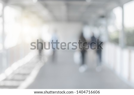 blur background image of empty modern sky walk way in city with people walking indoor and sunlight abstract gray blur bokeh. #1404716606