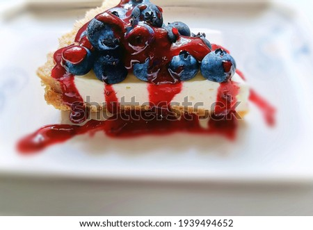 Blur background mode shooting close-up photo of a piece of fresh blueberry tart topped with mixed berries sauce, homemade.