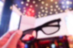 Blur background of boy holding 3D glasses and tickets