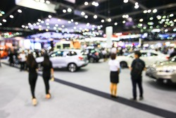 blur background of motorshow, car show room. Abstract blurred image people in cars exhibition show