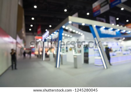 Blur background of people in photo camera fair expo at big exhibition hall event trade show room. Meetings, incentives, conferences and exhibitions (MICE) business and commercial trading concept.