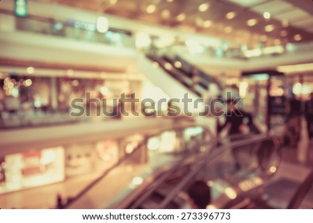 Blur background photograph of people in the department store building with huge escalator in retro color