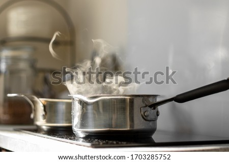 Blur background. Selective focus. Boiling water with steam in a pot on an electric stove in the kitchen