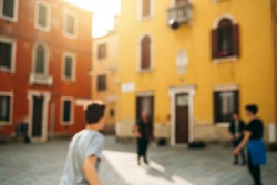 Blur background with three teens playing ball in the yard. Vinice, Italy.