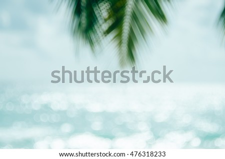 Blur beautiful nature green palm leaf on tropical beach with bokeh sun light wave abstract background. Copy space of summer vacation and business travel concept. Vintage tone filter color style. - Shutterstock ID 476318233