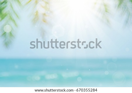 Blur beautiful nature green palm leaf on tropical beach with bokeh sun light wave abstract background.   - Shutterstock ID 670355284