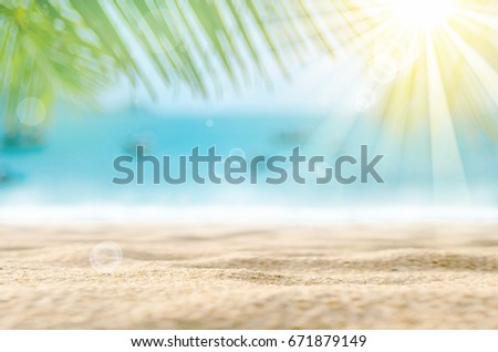 Blur beautiful nature green palm leaf on tropical beach with bokeh sun light wave abstract background.Copy space of summer vacation and business travel concept. Vintage tone filter effect color style