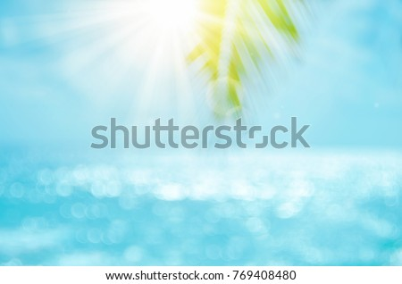 Stock Photo Blur beautiful nature green palm leaf on tropical beach with bokeh sun light wave abstract background. Copy space of summer vacation and business travel concept. Vintage tone filter effect color style