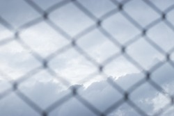 Blur black steel cage imprison the grey clouds and blue sky in the cloudy sadness day