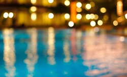 blur bokeh night light reflection in summer swimming pool Christmas party blue water abstract background