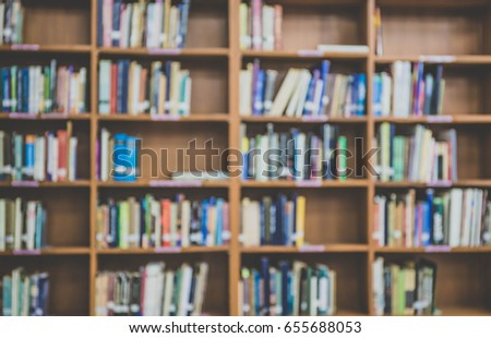 blur books on wooden bookshelf in university or public library room or book store,abstract blur background.concept for education,background.