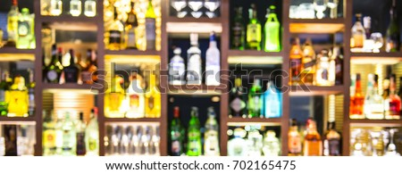 Blur bottles of spirits and liquor on bar counter #702165475