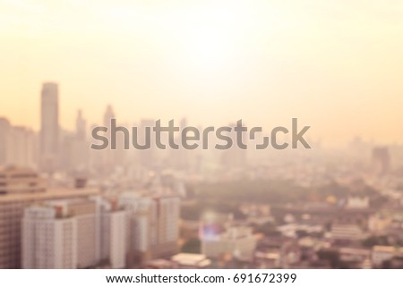 Blur cityscape background of city office towers and residential buildings in downtown CBD central business district with blurry horizon skyline in warm yellow gold illumination morning light  #691672399