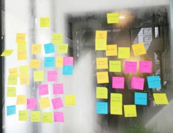 Blur color notes or sticky note on the glass wall in the office during brainstorming session in ideation workshop