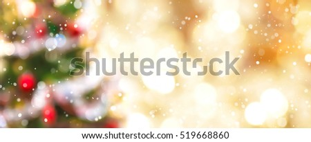 Blur colorful Christmas tree and gold bokeh in snow fall, festive theme panoramic banner background