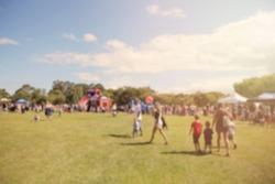 Blur defocused background of people in park fair, summer festival, family outdoors, festive fair