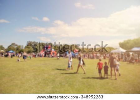 Blur defocused background of people in park fair, summer festival, retro tone