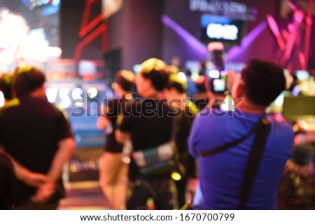 blur event with people background - blurred computer game show festival bokeh  - people and activity on stage - camera man - business concept