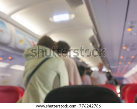 blur image of airplane 's interior , aircraft 's flight arrived the destination safely , passenger walk out of the plane to terminal building