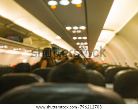 blur image of airplane 's interior , aircraft 's flight boarding passenger to their seat ,fly to the destination
