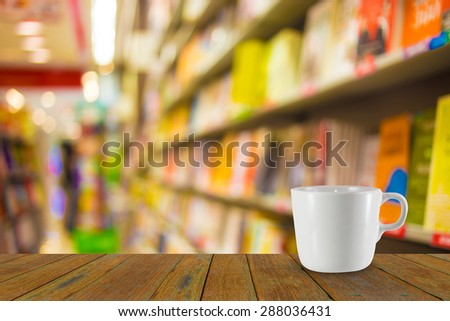 Blur image of coffee and book store on shelf at shopping center for background usage.